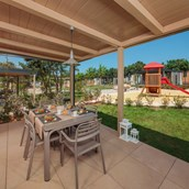 Luxuscamping: Spacious and covered terrace with barbeque - Mobilheim Mediterannean Garden Premium auf Camping Resort Lanterna
